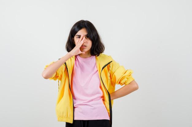 Tienermeisje houdt hand op gezicht, houdt hand op taille in t-shirt, jas en kijkt peinzend, vooraanzicht.