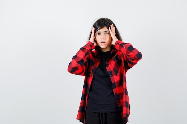 Tienermeisje houdt hand op gezicht in casual shirt en kijkt geschokt. vooraanzicht.