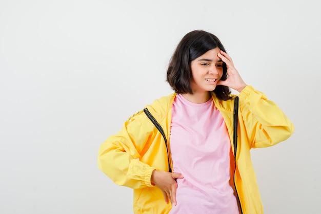 Tienermeisje houdt hand op het hoofd in t-shirt, jas en ziet er gestrest uit. vooraanzicht.