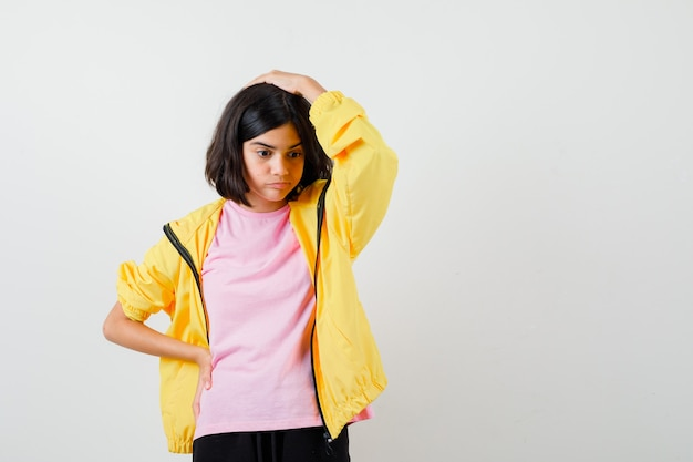 Tienermeisje houdt hand op hoofd en taille in geel trainingspak, t-shirt en kijkt verbaasd, vooraanzicht.