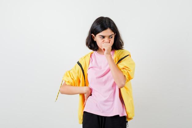 Tienermeisje houdt hand op mond en taille in geel trainingspak, t-shirt en kijkt verbaasd, vooraanzicht.
