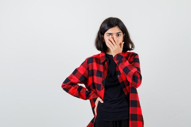 Tienermeisje houdt hand op mond in t-shirt, geruit overhemd en kijkt verbaasd. vooraanzicht.