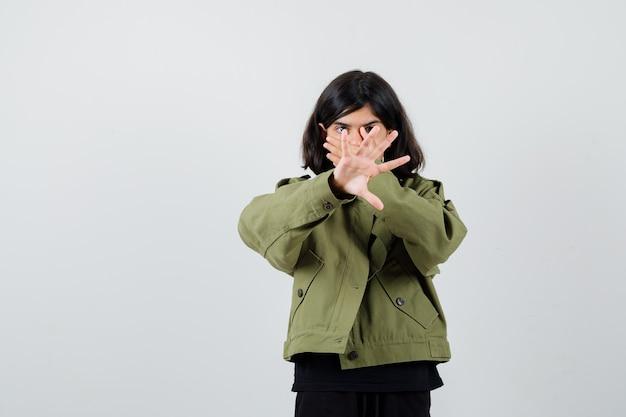Tienermeisje houdt hand op mond terwijl ze stopgebaar in t-shirt, jas toont en er walgelijk uitziet. vooraanzicht.