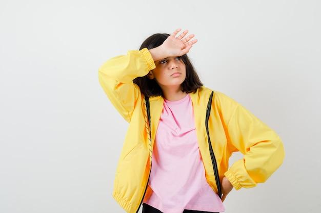Tienermeisje houdt hand op voorhoofd terwijl ze wegkijkt in t-shirt, gele jas en attent, vooraanzicht.