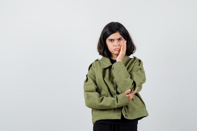 Tienermeisje houdt hand op wang in t-shirt, jasje en kijkt weemoedig. vooraanzicht.