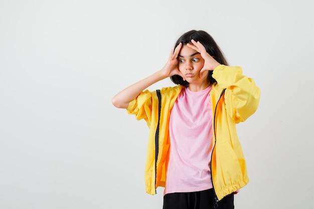 Tienermeisje houdt handen op gezicht in t-shirt, jas en kijkt peinzend, vooraanzicht.