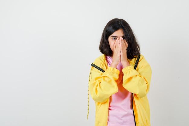 Tienermeisje houdt handen op gezicht in t-shirt, jas en ziet er hoopvol uit. vooraanzicht.