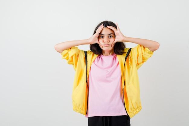 Tienermeisje houdt handen op het hoofd in t-shirt, jas en kijkt verveeld. vooraanzicht.
