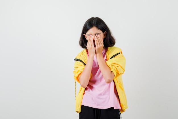 Tienermeisje houdt handen op ogen in geel trainingspak, t-shirt en kijkt boos, vooraanzicht.