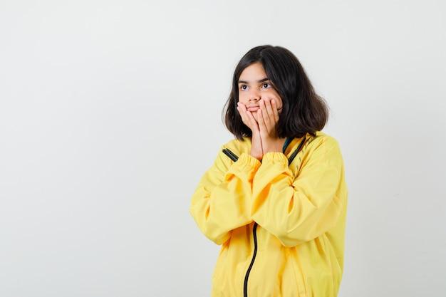 Tienermeisje houdt handen op wangen, kijkt weg in gele jas en kijkt verbaasd, vooraanzicht.