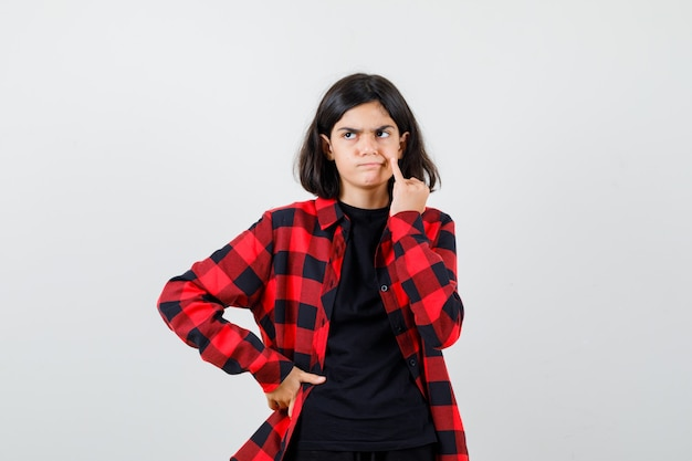 Tienermeisje houdt pink op wang in t-shirt, geruit hemd en kijkt ontevreden, vooraanzicht.