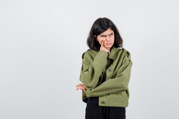Tienermeisje houdt vinger op de wang, kijkt weg, fronst gezicht in legergroen jasje en kijkt boos. vooraanzicht.