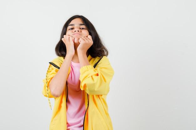 Tienermeisje houdt vuisten op wangen in geel trainingspak, t-shirt en kijkt ontevreden, vooraanzicht.