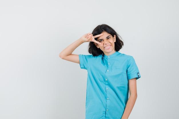 Tienermeisje in blauw shirt met v-teken over haar ene oog en kijkt vrolijk