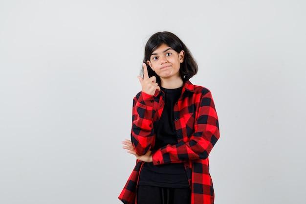 Tienermeisje in casual shirt dat naar boven wijst en peinzend kijkt, vooraanzicht.