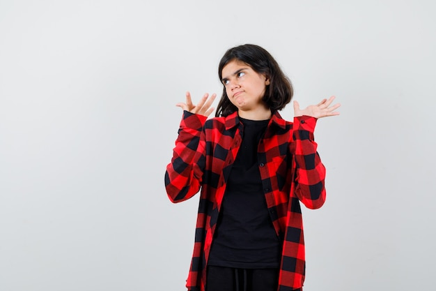 Tienermeisje in casual shirt die handen uitrekt in een verbaasd gebaar, opzij kijkt en peinzend kijkt, vooraanzicht.