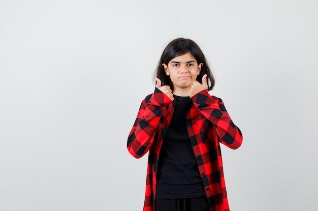 Tienermeisje in casual shirt duimen opdagen en er vrolijk uitzien, vooraanzicht.