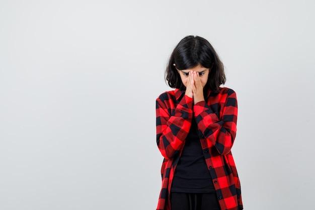 Tienermeisje in casual shirt hand in hand op gezicht en gefocust, vooraanzicht.