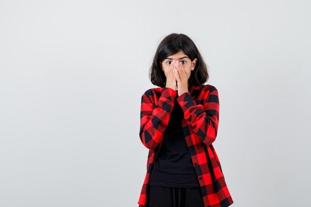 Tienermeisje in casual shirt hand in hand op gezicht en kijkt geschokt, vooraanzicht.