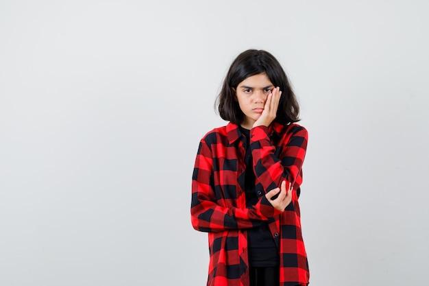 Tienermeisje in casual shirt leunend op de handpalm en kijkt boos, vooraanzicht.