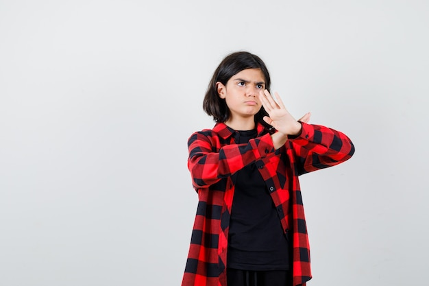 Tienermeisje in casual shirt met karate chop gebaar en zelfverzekerd, vooraanzicht.