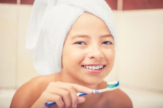 Tienermeisje in de badkamer met tandenborstel. mondhygiëne.