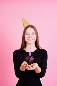 Tienermeisje in de gouden muffin van de verjaardagsholding met kaarsen, die een wens over roze achtergrond maken