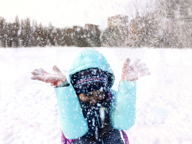 Tienermeisje in de winter openluchtpret en het werpen van sneeuw.