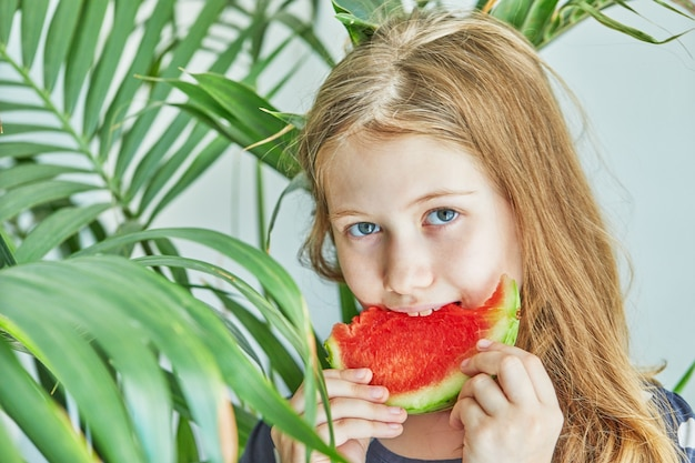 Tienermeisje in een blauwe jurk met stippen die een watermeloen eten.