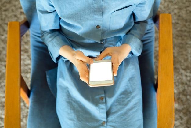 Tienermeisje in een blauwe jurk zittend op een fauteuil terwijl ze een slimme telefoon vasthoudt