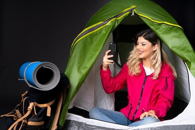 Tienermeisje in een camping groene tent