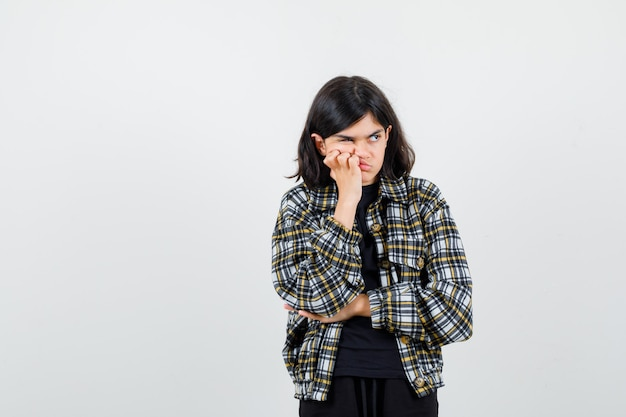 Tienermeisje in een casual shirt dat de hand op de wang drukt, wegkijkt en verveeld kijkt, vooraanzicht.