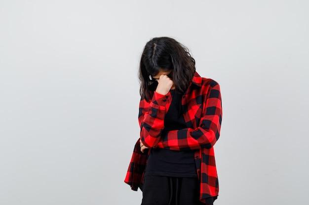 Tienermeisje in een casual shirt dat de hand op het gezicht houdt en er depressief uitziet, vooraanzicht.