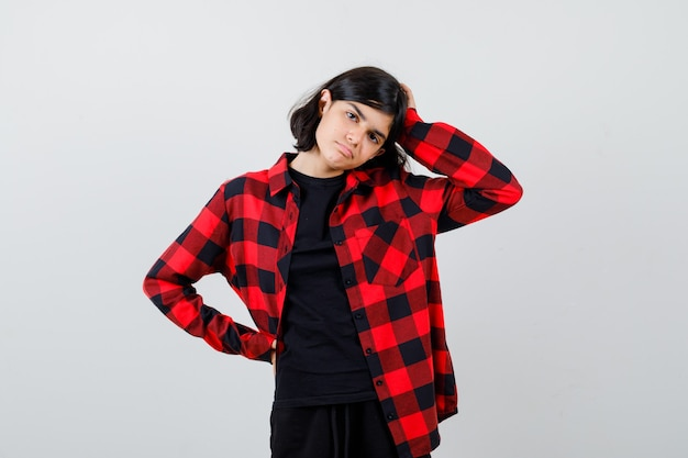 Tienermeisje in een casual shirt dat de hand op het hoofd houdt, de hand op de taille houdt en aarzelend kijkt, vooraanzicht.