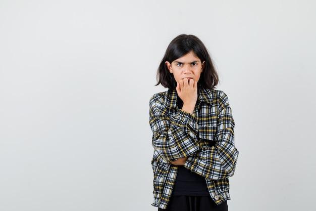 Tienermeisje in een casual shirt dat nagels bijt en er gestrest uitziet, vooraanzicht.