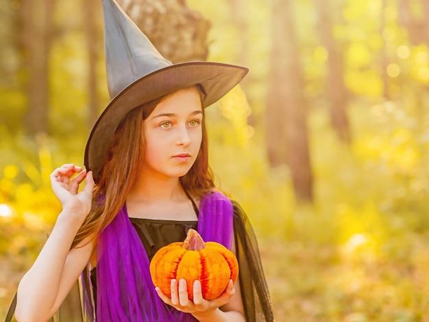 Tienermeisje in een halloween-kostuum in het bos met een pompoen. halloween