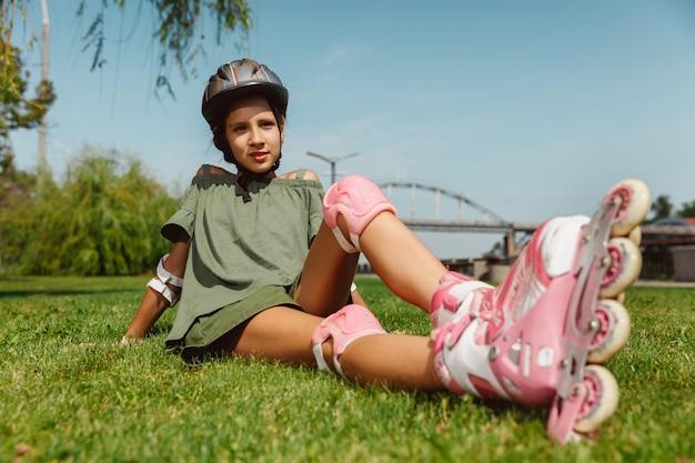 Tienermeisje in een helm leert buiten op rolschaatsen te rijden