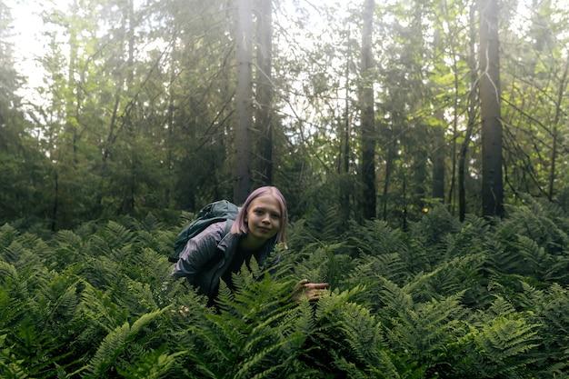 Tienermeisje in een mistig bos tussen varens is gepassioneerd door de natuur