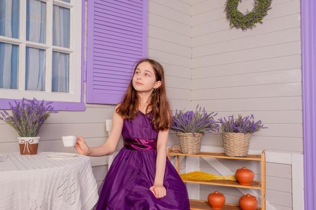 Tienermeisje in een paarse jurk binnenshuis. een meisje met blond haar in een mooie jurk. tiener, meisje