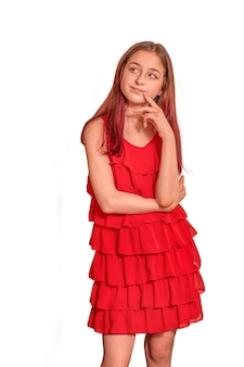 Tienermeisje in een rode jurk op een witte achtergrond. portret van een mooi meisje in studio, geïsoleerd.