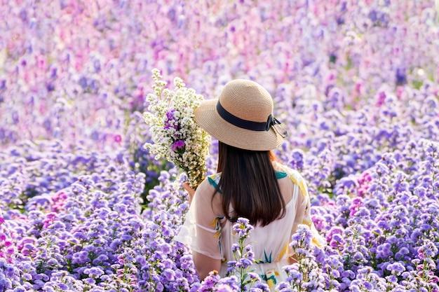 Tienermeisje in een tuin van bloemen jong gelukkig aziatisch meisje in margaret aster bloemen veld in garde