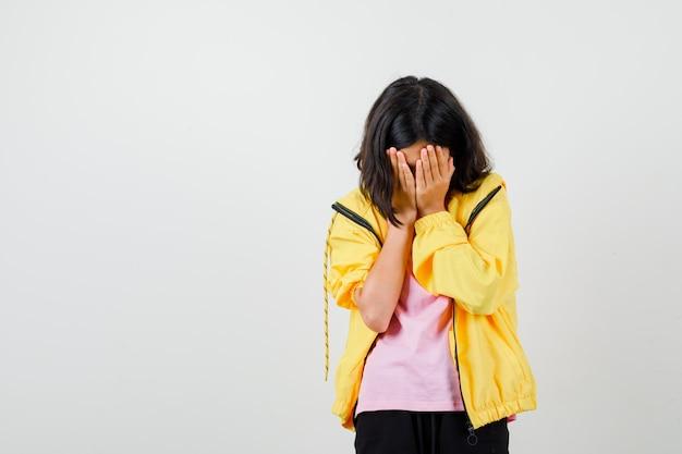 Tienermeisje in geel trainingspak, t-shirt dat gezicht bedekt met handpalmen en er bedroefd uitziet, vooraanzicht.