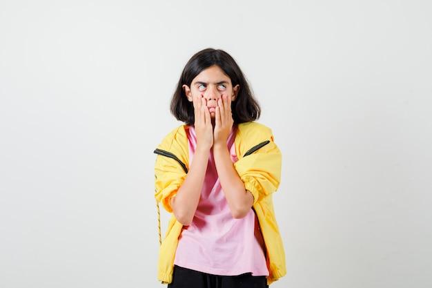 Tienermeisje in geel trainingspak, t-shirt dat haar gezicht naar beneden trekt en er ontevreden uitziet, vooraanzicht.