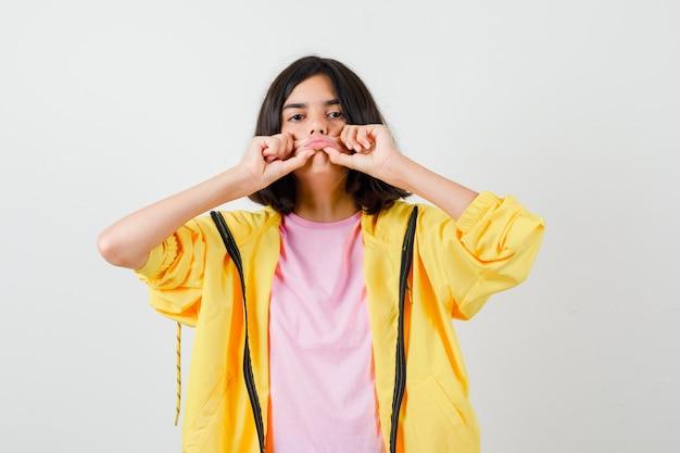 Tienermeisje in geel trainingspak, t-shirt dat haar lippen vasthoudt en uitrekt en weemoedig kijkt, vooraanzicht.
