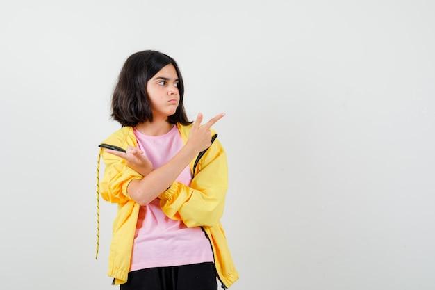 Tienermeisje in geel trainingspak, t-shirt dat opzij wijst met gekruiste armen en er attent uitziet, vooraanzicht.