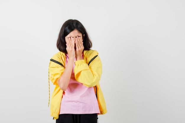 Tienermeisje in geel trainingspak, t-shirt hand in hand op gezicht en boos, vooraanzicht.