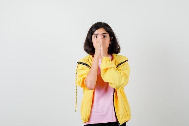 Tienermeisje in geel trainingspak, t-shirt hand in hand op gezicht en ziet er bang uit, vooraanzicht.