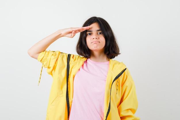 Tienermeisje in geel trainingspak, t-shirt saluerend met de hand op het voorhoofd en zelfverzekerd, vooraanzicht.