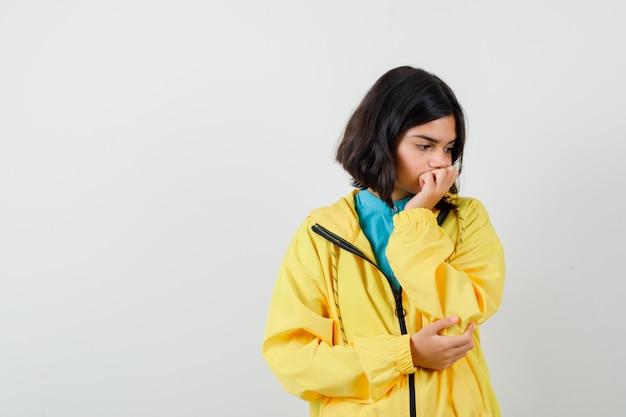 Tienermeisje in gele jas die aan iets denkt, naar beneden kijkt en er somber uitziet, vooraanzicht.