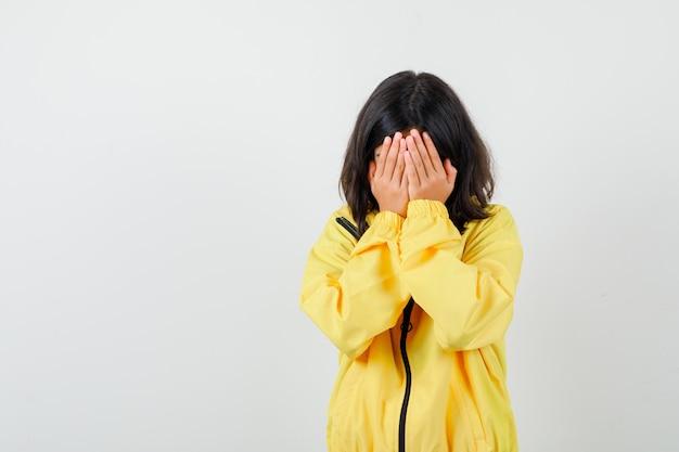 Tienermeisje in gele jas die gezicht bedekt met handen en er depressief uitziet, vooraanzicht.